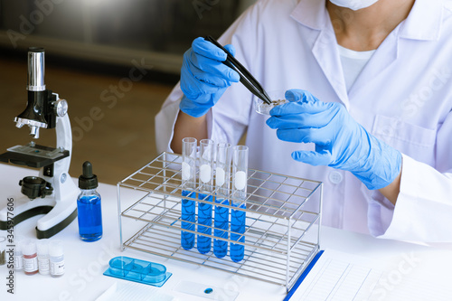 Fotografia scientists researching in laboratory in white lab coat, gloves analysing, lookin