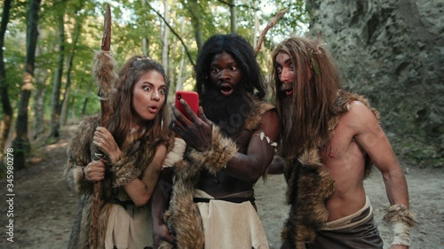 Canvas Print Cheerful group of neanderthal hunters using modern technology smartphone cheering up walking outside cave in the jungle