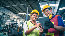 Two Multiethnic Industrial Workers Looking At Tablet In The Warehouse.