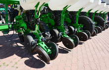 A Close-up On Agricultural Farm Machinery, Sowing Drill Mechanical Seeder And Fertilizer Machine Tractor Attachment.