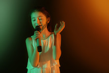 Cute Little Girl Singing Against Dark Background