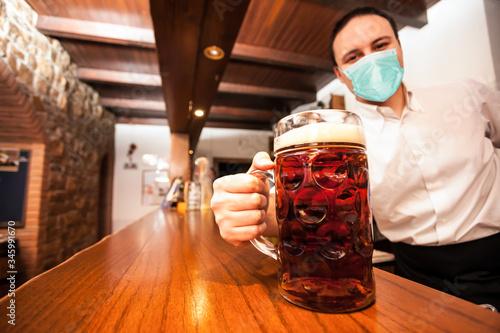 Fototapeta Masked bartender serving a giant beer obraz