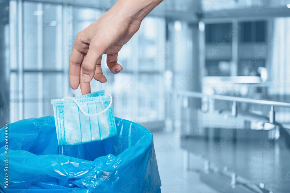 Fototapeta A hand throws a disposable mask into a trash bin