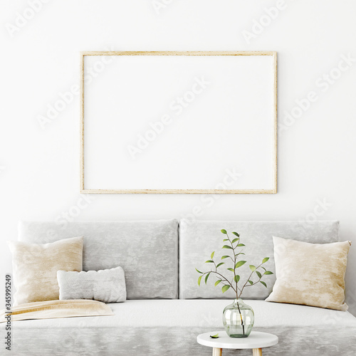 Fotomural Poster mockup with horizontal frame hanging on the wall in living room interior with sofa, beige pillows and green branch in glass vase on empty white background