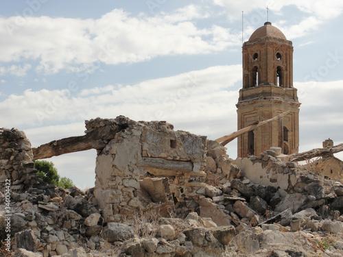 Ruinas de un antiguo pueblo con la torre de la iglesia destruido por la guerra Wallpaper Mural
