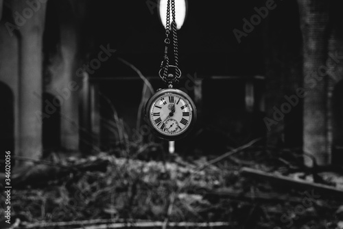 Photo Antique watch with chainlet hanging over heap of bricks and wood in an abandone catholic church