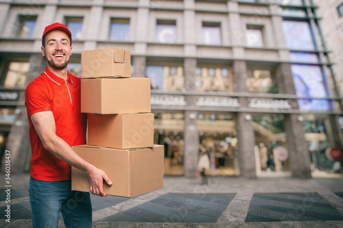Canvastavla Red courier outside carries parcels for deliveries of shipments.