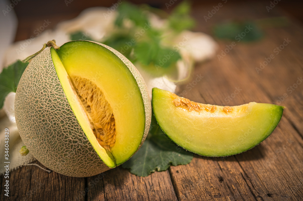 Fototapeta Whole and Slice of Melons with Leaves on wooden background, yellow melon or cantaloupe melon with seeds isolated on wooden background