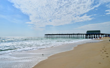 A Seascape View Of A Wooden Fishing Pier Extending Into The Green Foamy Waves Of The Atlantic Ocean.  Kitty Hawk, Outer Banks, North Carolina.  Copy Space.