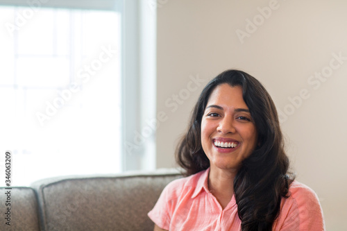 Young Hispanic woman smiling sitting on a sofa.