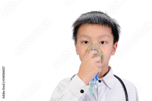 Photo A good looking Asian boy wearing white shirt using a respirator mark to treat and alleviate the symptoms caused by the respiratory system on isolate of white backgrounds