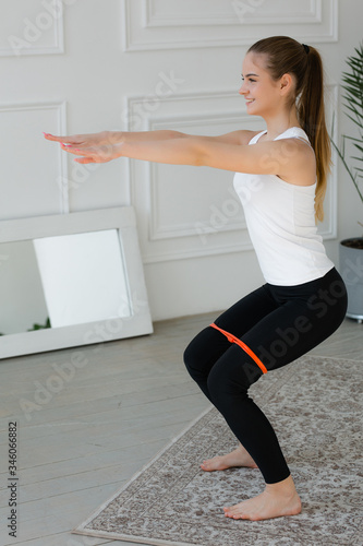 Fitnes trainer girl has legs shoulder width apart, does a squat with an expander Slika na platnu