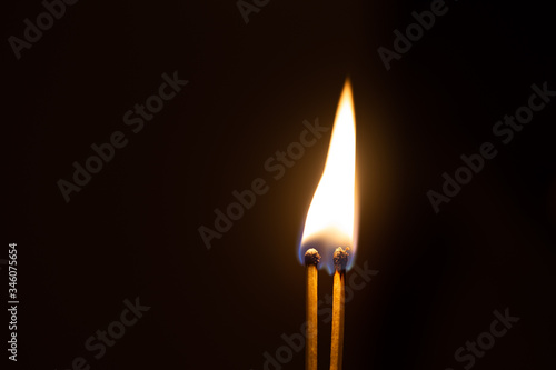 Couple of matches burning together with heat flame isolated on a black background