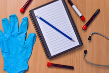 Notebook With Vacuum Tubes For Blood Collection And Rubber Gloves On A Wooden Table