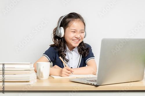 Fototapeta Asian primary school girls taking online classes obraz
