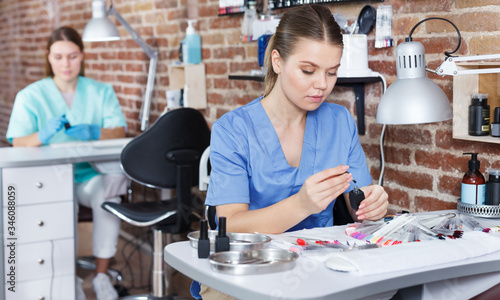 Photo Nail master in gloves at working place in salon