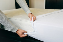 Man Covering A Mattress With A Mattress Protector