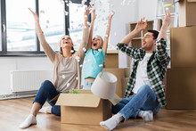 Mortgage, Family And Real Estate Concept - Happy Mother, Father And Little Daughter Playing With Packing Foam Peanuts At New Home
