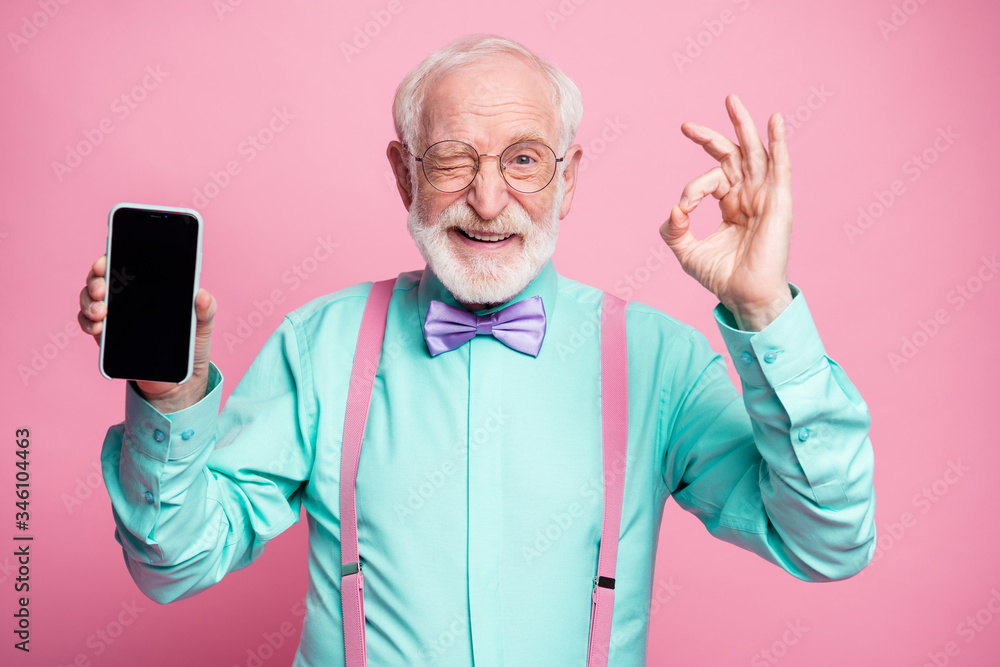 Fototapeta Portrait of energetic positive old man hold new cellphone show okay sign recommend choose good modern technology wear teal turquoise shirt violet bow tie isolated pastel pink color background