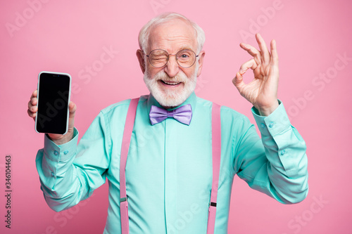 Obraz Portrait of energetic positive old man hold new cellphone show okay sign recommend choose good modern technology wear teal turquoise shirt violet bow tie isolated pastel pink color background - fototapety do salonu