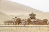DUNHUANG,CHINA-MARCH 11 2016: Temple at Mingsha shan Gobi desert, sand mountain and Crescent moon lake in Dunhuang, silk road at Gansu, northwest of China - 346113268