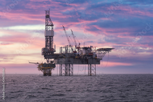 Drilling rig with oil and gas platform is working at offshore for producing crude oil, natural gas and produced water in petroleum industry that shows the steel construction of heavy platform and rig.
