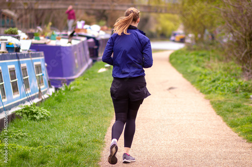 Fotografie, Obraz Sporty lady jogging along the towpath in Hackney, London