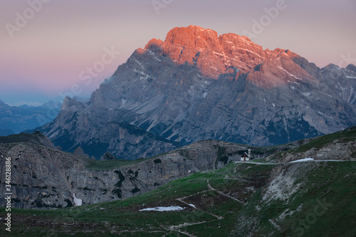 Mountain landscape in the European Dolomite Alps underneath the Three Peaks with alpenglow during sunrise, footpath leading to chapel, South Tyrol Italy фототапет