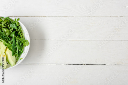 Fotografia, Obraz top view of arugula, avocado in bowl on white wooden surface