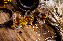 Small Tasting Glasses With Aged Scotch Whisky On Old Dark Wooden Vintage Table With Barley Grains