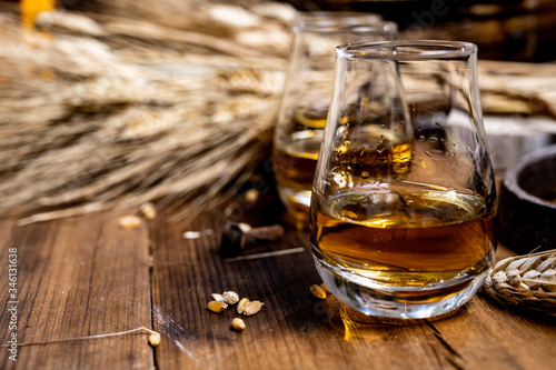 Photo Speyside scotch whisky tasting on old dark wooden vintage table with barley grai