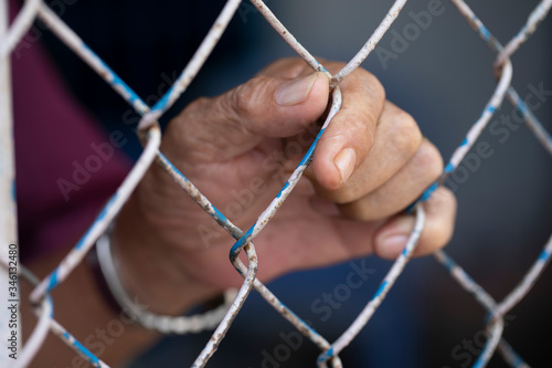 Photo the hand of a man holding on to a cyclone wire fence