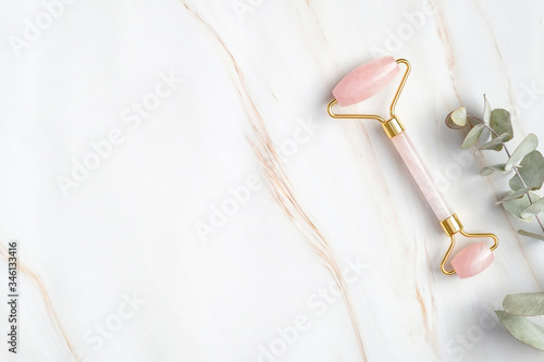 Rose quartz face roller and eucalyptus leaf on marble background, top view Fototapete