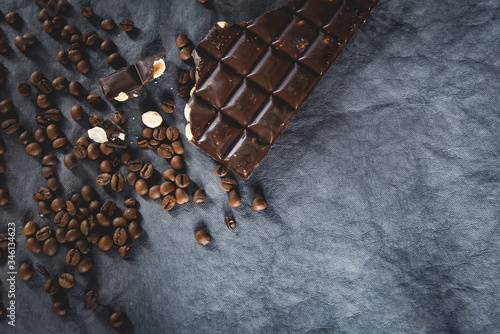 Photo Dark roast coffee beans scattered on dark background with bar of bitter chocolate and nuts