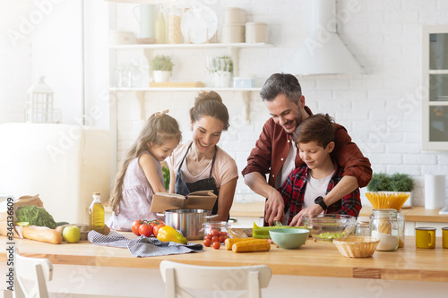 Tela Happy family cooking together on kitchen with kids.