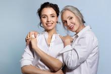 Loving Senior Mother Hugging Adorable Adult Daughter Portrait.