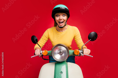 Fototapeta Portrait of her she nice attractive lovely crazy glad positive cheerful cheery girl driving moped traveling having fun isolated on bright vivid shine vibrant red color background obraz