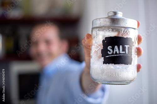 Photo primo piano di barattolo di vetro con sale tenuto da un ragazzo