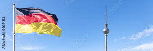 Flag of Germany and TV Tower of Berlin with blue sky, panoramic picture Canvas Print