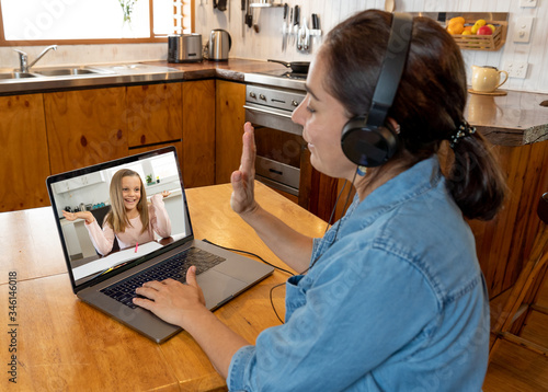 Photo Teacher with laptop working from home online teaching student in live video class