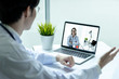 Asian doctor man wearing stethoscope white coat video call with woman doctor in his office.