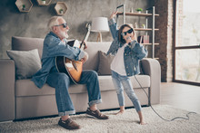 Photo Of Two People Grandpa Play Guitar Little Granddaughter Mic Singing Rejoicing Cool Style Trendy Sun Specs Denim Clothes Repetition School Concert Stay Home Quarantine Living Room Indoors