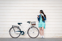 Young Girl Consulting Her Phone While Having A Drink And Resting From Her Bike Ride