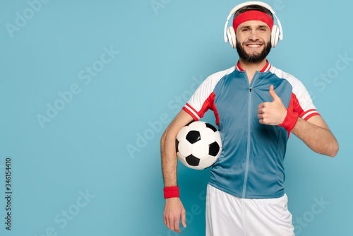 Obraz na plátne happy stylish sportsman in headphones with soccer ball showing thumb up on blue