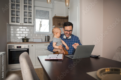 Young father working remotely while babysitting his son. Canvas Print