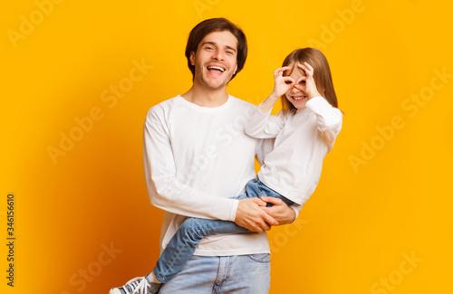 Obraz Playful girl and dad having fun on yellow background - fototapety do salonu