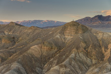 A Lone Man Stands On Top Of A Peak Next To Manly Beacon In Death Valley, California, USA.