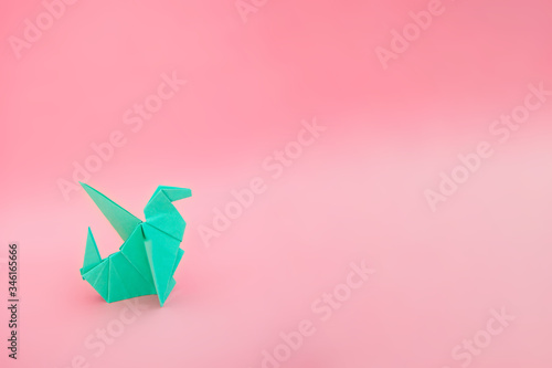 Fototapeta Turquoise origami dragon on the pastel paper background
