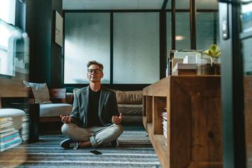 Businessman meditating in lotus pose