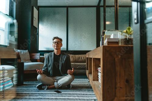 Fotografia Businessman meditating in lotus pose